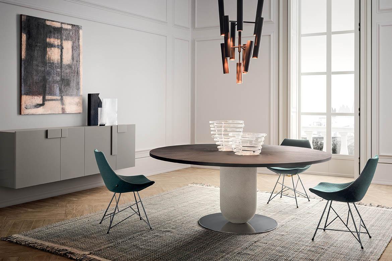tavolo rotondo con piano in legno borgogna e colonna centrale in cemento e piatto base in metallo. sedie gamma con traliccio. madia sospesa in laccato opaco tortora