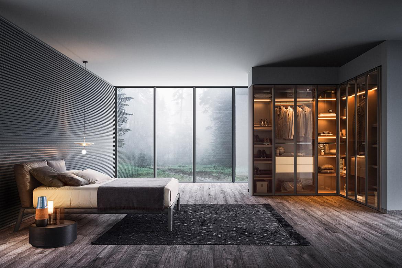 armadio angolare su misure con ante in vetro trasparente, letto dioniso in legno massello, comodino rotondo dedalo, tappeto teseo tessoria asolana Pianca