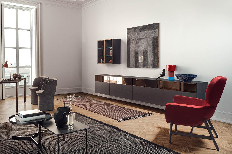 credenza sospesa con frontali in specchio bronzo e legno rovere grigio, vetrina venere fissata alla parete poltrona rossa laurie design Calvi Brambilla