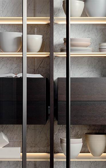armadio con ante in vetro trasparente, schiena in marmo materico, cassettiere sospese in legno pianca