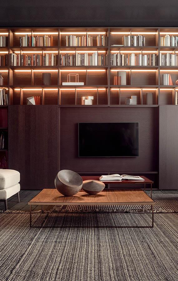 libreria con luci e con porte scorrevoli in legno che nascondono il televisore, tavolini icaro con struttura in metallo e piano in legno pianca