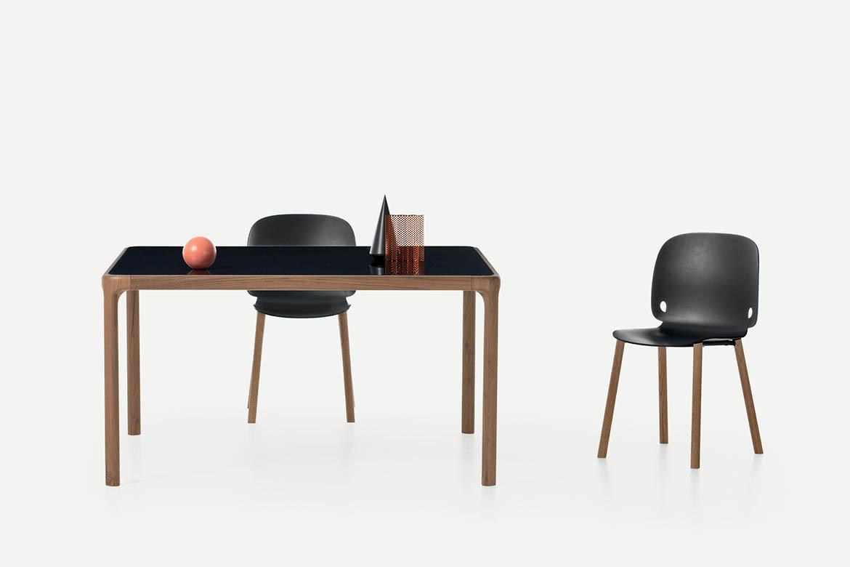 tavolo inari con piano in vetro e struttura in legno sedie con seduta in poliuretano nero e gambe in legno pianca